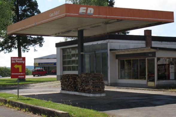 Tankstelle mit Holzstapeln an Stelle von Zapfsäulen